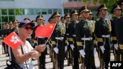Човек вее знамиња на Кина и на Хонг Конг