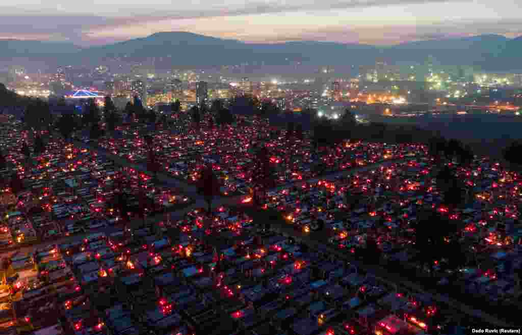 The glow of candles and lamps from the cemetery on Crkvicko hill cemetery with the city lights of Zenica in the background