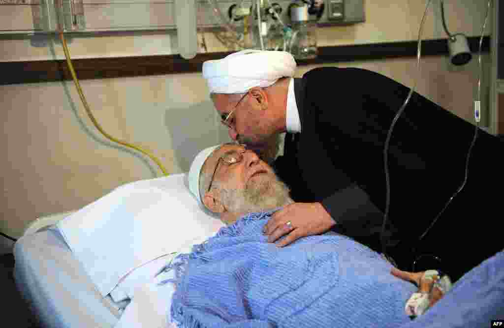 Iranian President Hassan Rohani visits Supreme Leader Ayatollah Ali Khamenei after his prostate operation at a hospital in Tehran. (AFP via Khamenei's website)