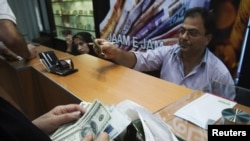 A woman counts U.S. dollars at a currency-exchange shop in a Tehran shopping center on October 3.