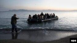 Греческий рыбак помогает вытащить на берег лодку с сирийскими беженцами, май 2015 года