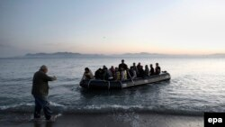 Греческий рыбак помогает вытащить на берег лодку с сирийскими беженцами, май 2015 года.