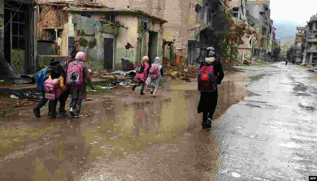 Syrian girls walk in the rain as they return from school in the southwestern city of Daraa. The bombardment of the city has ended amid a shaky cease-fire and Syrian children in the city have been able to return to school. (AFP/Fadi Dirani)