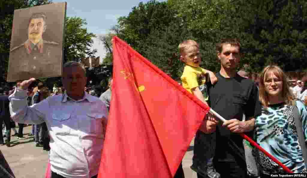 Мужчина держит портрет Сталина, рядом молодой человек держит флаг Советского Союза. Алматы, 9 мая 2013 года.