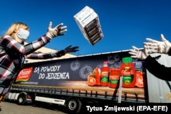 Workers load a truck with food aid in Bydgoszcz, Poland, on April 8. Two Polish companies, Polski Cukier and Polskie Przetwory, donated food products to help those most in need because of the coronavirus pandemic.