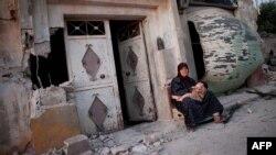 Žena sedi sa unukom ispred srušenog doma u Tremzi