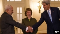Iranian Foreign Minister Mohammad Javad Zarif (left) shakes hands with U.S. Secretary of State John Kerry (right) as EU envoy Catherine Ashton looks on at nuclear talks on November 20.