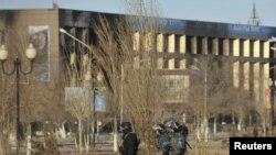 Полицияның қарулы жасағы Жаңаөзеңдегі орталық алаңмен кетіп барады. 19 желтоқсан 2011 ж.