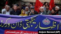 "Pakistani journalists and rights activists hold a banner reading ""Solidarity With Dawn Workers"" during a demonstration in Islamabad on December 5."
