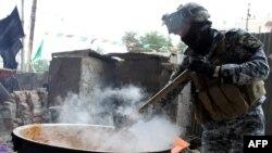 شرطي عراقي يساهم في طبخة بمناسبة عاشوراء.