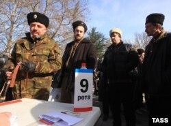 Члены так называемой крымской самообороны в Симферополе 23 февраля этого года. Вынужденные переселенцы из Крыма утверждают, что самооборона занималась запугиванием и принуждала некоторых активистов покинуть Крым