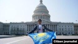 Молодой человек с казахстанским флагом перед зданием Капитолия в Вашингтоне.