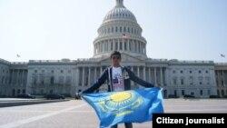 Молодой человек с казахстанским флагом фотографируется на фоне Капитолия в Вашингтоне.