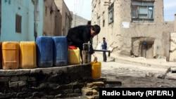 یک کودک افغان حین گرفتن آب از یک بمبه