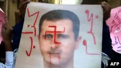 An image grab taken from a video uploaded on YouTube allegedly shows antiregime protesters holding a defaced poster of President Bashar al-Assad in the Qadam neighborhood of Damascus in early November.