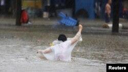 Пешеход передвигается по затопленной после обрушившегося тайфуна улице. Провинция Гуандун, 16 сентября 2018 года.