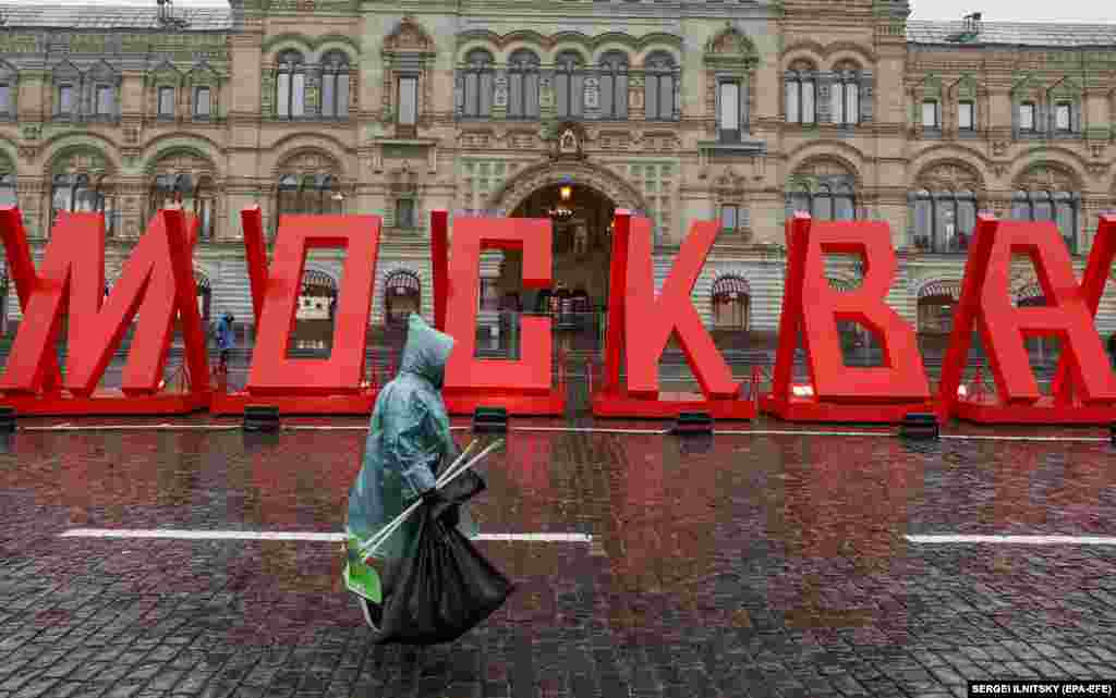 A municipal worker in the Russian capital walks past a sign at an exhibition commemorating the battle for Moscow during World War II. (epa-EFE/Sergei Ilnitsky)