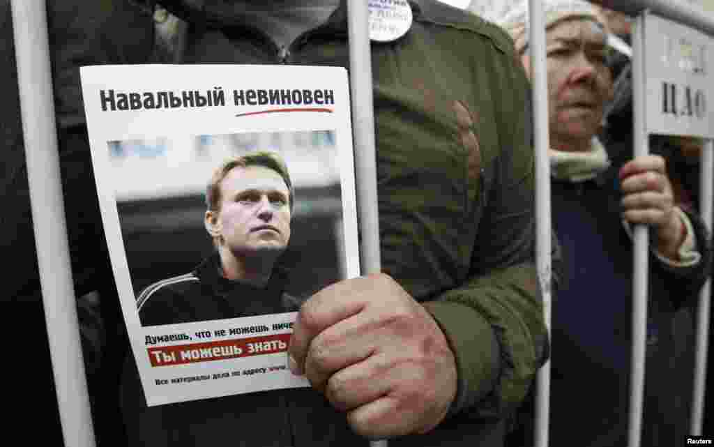 A man holds a portrait of opposition figure Aleksei Navalny.