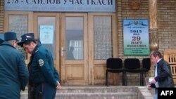 Ташкент көшесінде тұрған өзбек полицейлері мен олардың жанынан өтіп бара жатқан азамат. Өзбекстан, 29 наурыз 2015 жыл. (Көрнекі сурет)