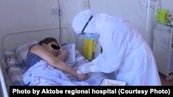 Медик в защитном костюме и пациентка в «красной зоне» медицинского центра в Актобе.