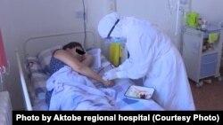 Ақтөбе медицина орталығында науқасқа дәрі салып жатқан медицина қызметкері.
