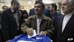 Iran's new election law is seen by some as the outcome of a power struggle between President Mahmud Ahmadinejad (center) and Supreme Leader Ayatollah Ali Khamenei.