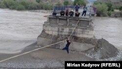 Жители Ак-Талинского района перебираются на противоположный берег по веревке.