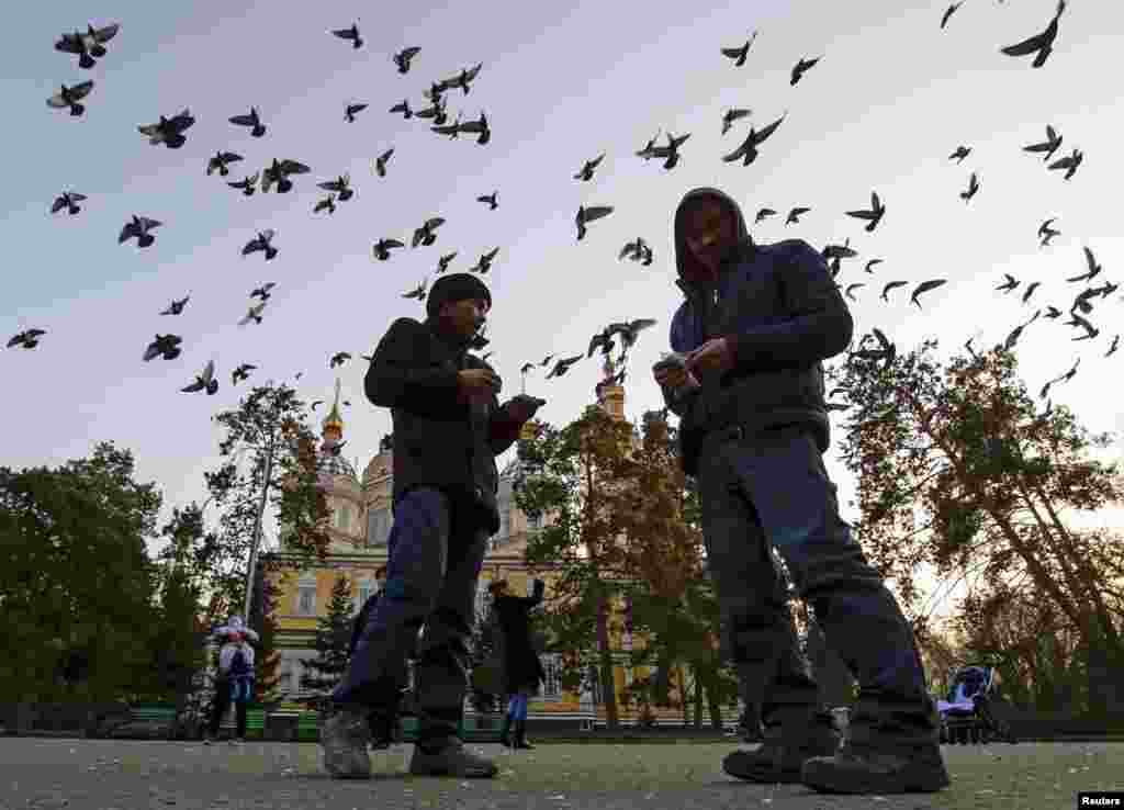 People feed pigeons in front of a cathedral in a park in Almaty, Kazakhstan, on December 4. (Reuters/​Shamil Zhumatov)