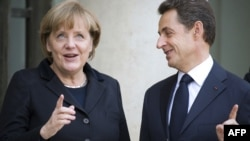 French President Nicolas Sarkozy (right) welcomes German Chancellor Angela Merkel prior to a working lunch at the Elysee Palace in Paris on December 5.