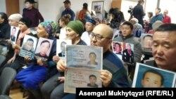 Люди на пресс-конференции в Нур-Султане с фотографиями родственников, удерживаемых, по их словам, под стражей в Китае. 27 ноября 2019 года.