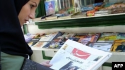 "Iran -- An Iranian woman reads the front page of a newspaper ""Sharq"" in Tehran, 11Oct2003"