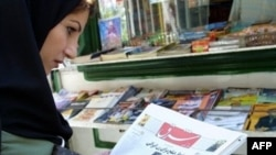 "An Iranian woman reads the front page of ""Sharq"" in Tehran."