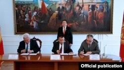 Қырғызстан парламентіндегі үш партия жетекшілері үкіметтік коалицияны құру туралы келісімге қол қойып жатыр. Бішкек, 31 наурыз 2014 жыл.