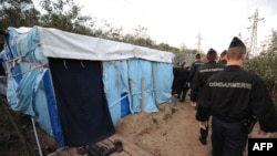 """French police arrive to dismantle the makeshift tents of would-be immigrants in a wooded area known as """"The Jungle"""" in Calais."""