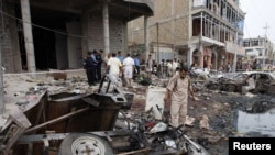 Residents inspect the site of a bomb attack that in Basra on May 10, one of a series of deadly attacks.