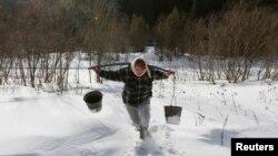 Оксана Ширшова несет коромысло с двумя ведрами воды из реки Терёл в селе Верхняя Бирюса, расположенном в тайге вблизи Красноярска