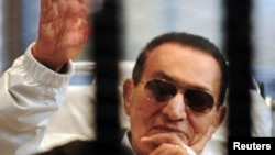 Egypt -- Former President Hosni Mubarak waves to his supporters inside a cage in a courtroom at the police academy in Cairo, April 13, 2013