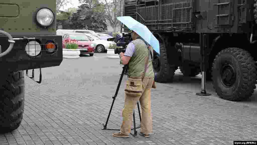 Телеоператору приходится работать под зонтом
