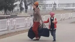 Turkmenistan. Mother with a big bags and child walking. Streets of Ashgabat. Living houses. January 2020
