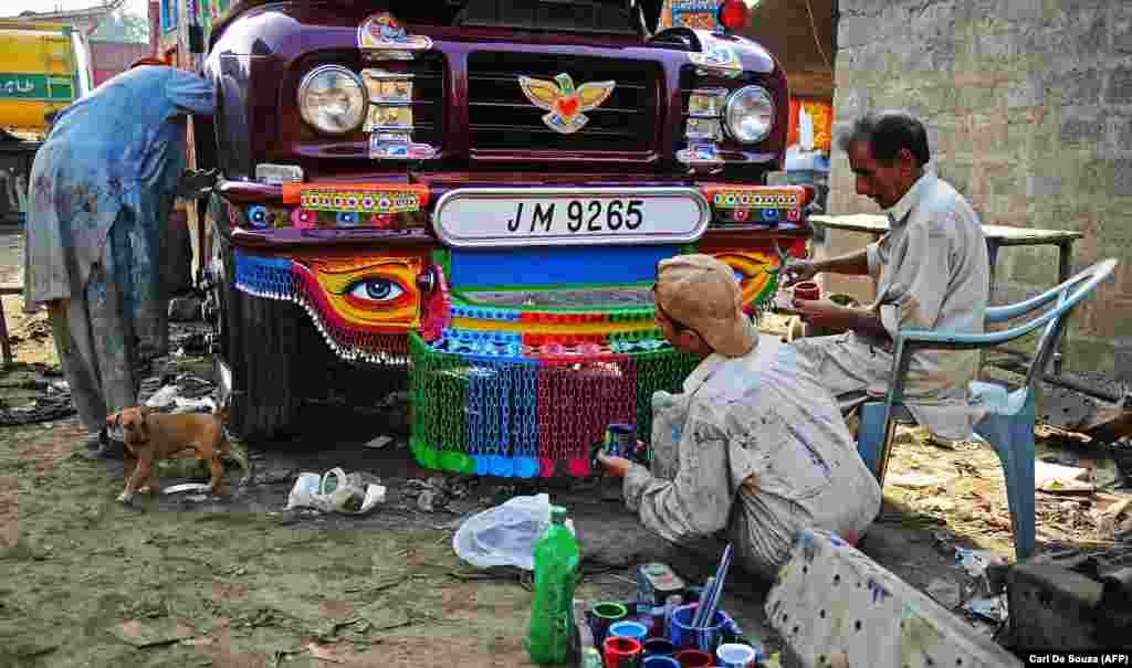 Главный художник по росписи грузовиков Хуссейн Нур (справа) и другие рабочие в мастерской Нура в Равалпинди.