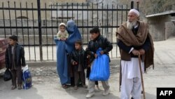 Afghan families wait to enter Pakistan at the Torkham border crossing between Afghanistan and Pakistan on February 17.