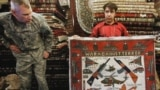 AFGHANISTAN -- an Afghan carpet trader displays a carpet showing different weapons