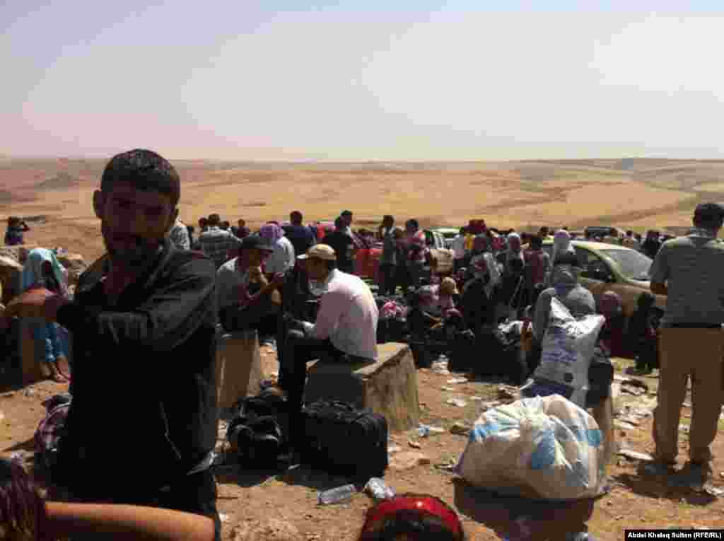Kurdish refugees wait on the Iraqi side of the border after arriving from Syria.