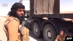 Iraq -- A video grab allegedly shows Shaker Wahib al-Fahdawi (L), the leader of Ussud Al-Anbar talking to Syrian truck drivers (R) after stopping their convoy at a highway at an undisclosed location in Anbar province, undated