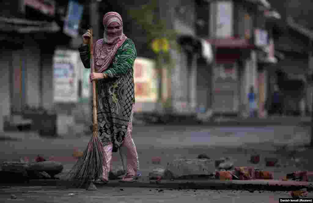 A woman removes rubble from a road on the Indian side of the restive Kashmir region. (Reuters/Danish Ismail)