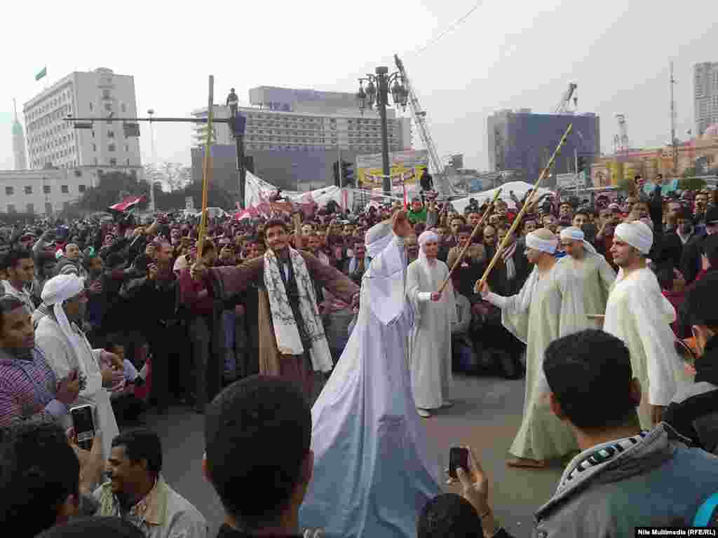 "Here in Tahrir Square, Egyptian dancers perform a traditional ""Dance of Sticks"" to entertain protesters."