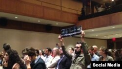 "Student Ali Abdi holds a ""End Sanctions Against Iran"" sign at an event in New York where Iranian Foreign Minister Mohammad Javad Zarif was speaking."