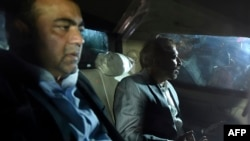 Pakistani Muttahida Qaumi Movement (MQM) political party top leader Farooq Sattar (R) and lawmaker Khawaja Izhar ul Hassan look on as they sit in a car after their arrest by paramilitary rangers in Karachi on August 22.