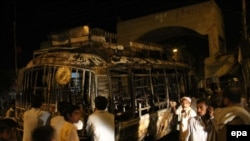 People gather near a bus that was set on fire by a mob in the southern Pakistani port city of Karachi on May 20.