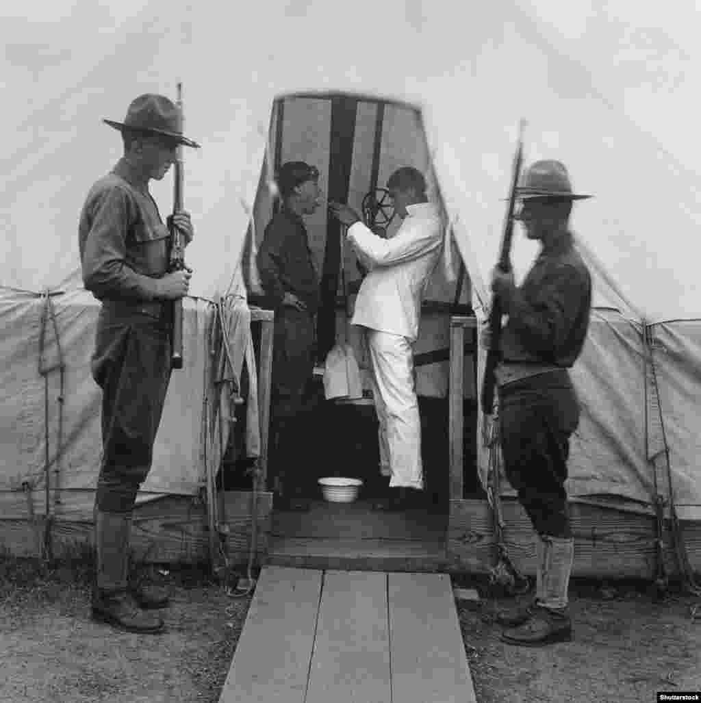 """Американски войник получава дезинфекционен спрей за гърло, което по-късно ще се окаже неефективно. Може би най-необичайният опит за спиране на пандемията обаче е така наречената """"черна сватба"""", проведена в Одеса в днешна Украйна. Черните сватби донякъде са еврейски ритуал за предпазване от мор, в които се женят двама от """"най-нещастните"""" на обществото в сложна церемония, проведена в гробището. Една такава сватба се е състояла в гробището в Одеса на 1 октомври 1918 г. Необикновеното бракосъчетание било отпразнувано с пиршество и двойката била """"обсипана със скъпи подаръци""""."""